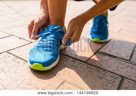 Woman try to fix shoes lace at outdoor