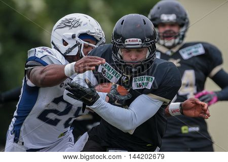MOEDLING, AUSTRIA - MAY 24, 2015: DB Christian Bobo (#28 Devils) tackles RB Anton Wegan (#9 Rangers) in a game of the Division I of the Austrian Football League.