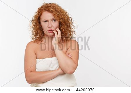 Thoughtful mature woman posing isolated on white. Beautiful red haired lady in white dress thinking about something. Expressing emotions concept.