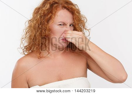 Bad smell makes this woman cover her nose. Picture of mature woman holding her nose isolated on white background in studio.