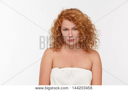 Picture of begging mature or senior woman with red hair looking at camera while posing isolated on whte background in studio. Emotions concept.