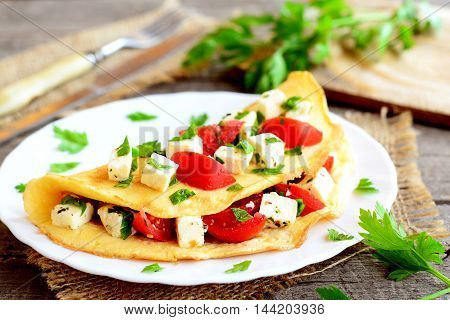Stuffed omelette on a plate. Fried omelette stuffed with cheese, tomatoes and parsley. Breakfast recipe. Closeup