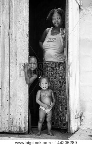 KARA, TOGO - MAR 9, 2013: Unidentified Togolese children and their mother at the porch of a house. Children in Togo suffer of poverty due to the unstable econimic situation