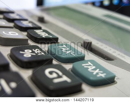 Dusty old calculator with shallow depth of field with focus centred on the minus tax button