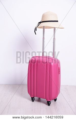 pink luggage case with white wall background