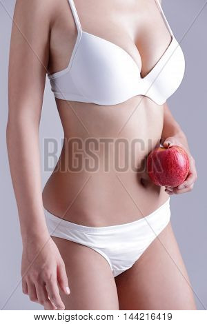 Fit woman hold apple isolated on the gray background asian