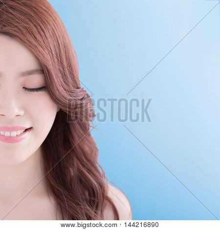 beauty woman close eyes and smile to you with isolated blue background asian
