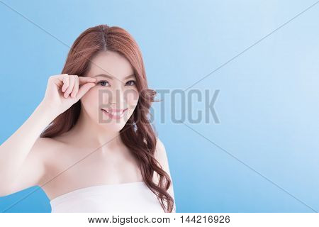 Woman face and eye care and she touch eye with hands asian beauty. Isolated over blue background asian beauty