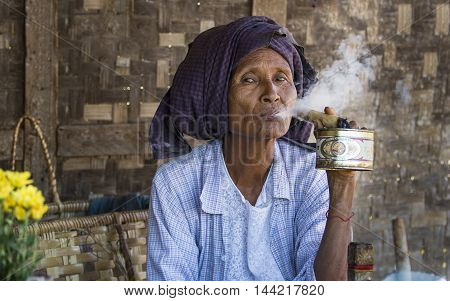 Bagan, Myanmar, September 2014: Old woman smoking a cigar