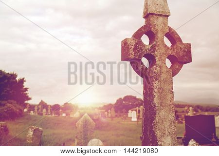 ancient monument and burial concept - old grave cross, headstones and ruins on celtic cemetery graveyard in ireland