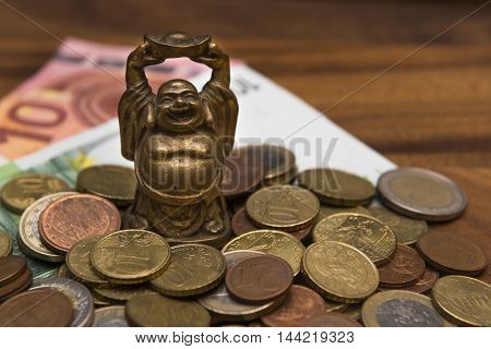 Talisman netske Hotei coins Euro banknotes on a wooden table