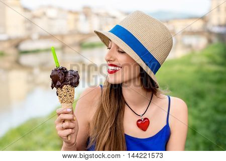 Young female tourist in blue dress holding chocolate ice cream in waffle cone sitting near the river in Florence city. Eating traditional italian ice cream gelato.