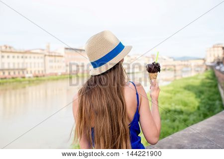 Young female tourist in blue dress holding chocolate ice cream in waffle cone sitting near the river in Florence city. Eating traditional italian ice cream gelato. Rear view