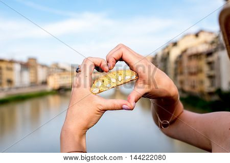 Female hands holding cantuccini cookie on the river background in Florence city in Italy. Cantuccini is traditional italian almond biscuits