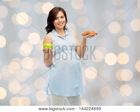 pregnancy, healthy eating, junk food and people concept - happy pregnant woman choosing between green apple and croissant over holidays lights background