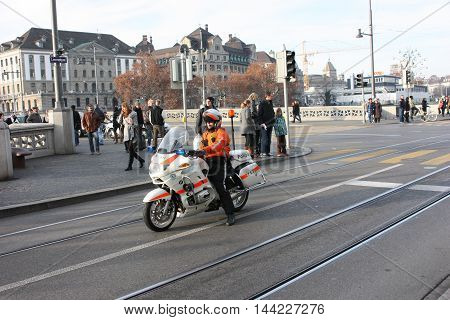 Zurich, Switzerland - November 26, 2011. A police officer on a motorcycle accompanying the demo