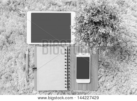 Closeup brown note book brown pen computer notebook tablet phone and artificial plant on gray fabric carpet textured background in top view in work concept in black and white tone