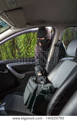 Thief in a mask stealing a bag from the car poster