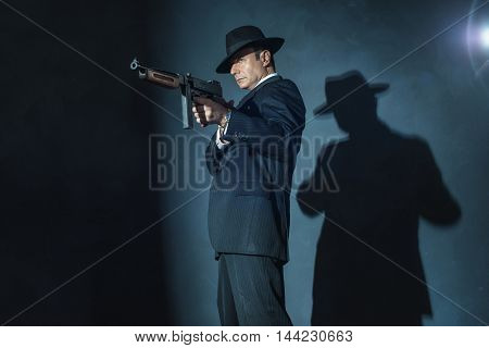 Film noir gangster shooting with a gun.