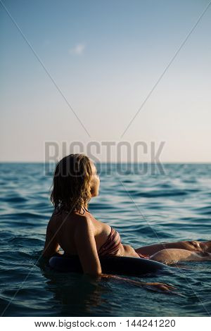 Rear view of unrecognizable young woman with short hair in bikini swimming on air ring with widened arms and looking away at seascape.Copy space