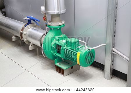 The pump circulating the green colour established in a boiler-house