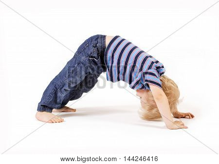Beautiful child. Small child carries out physical exercises on a white background. Concept of yoga, sport and health.