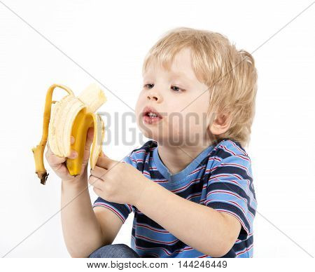 Child sit on a white background and eats banana