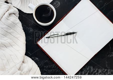 Soft knit sweater blanket with a hot cup of coffee and an open book with pen over grungy chalkboard background with room for copy space. Shot from overhead.