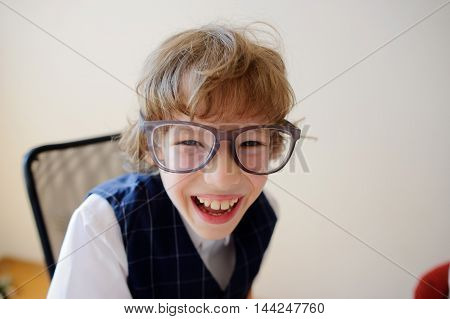 Funny little schoolboy in huge glasses carelessly laughing. He has a great mood. This elementary school student.