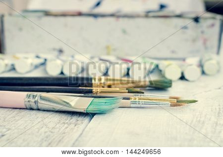 Artist paint brushes and oil paint tubes on white wooden background. Brush, paint, artistic. Tools for creative work. Back to school. Paintings Art Concept. Selective focus. Copy space.