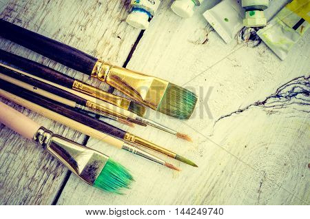 Artist paint brushes and oil paint tubes on white wooden background. Brush, paint, artistic. Tools for creative work. Watercolor paintbox. Back to school. Paintings Art Concept. Top view. Copy space.