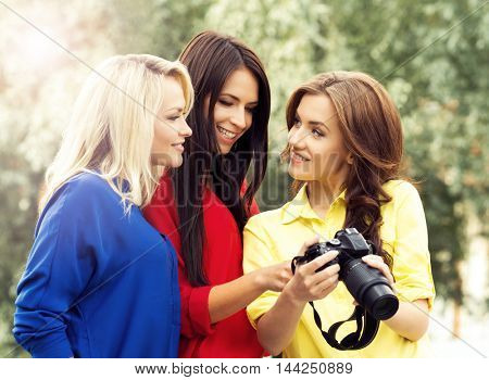Girls watching photos. Three beautiful women having a photosession in the park with a dslr camera.