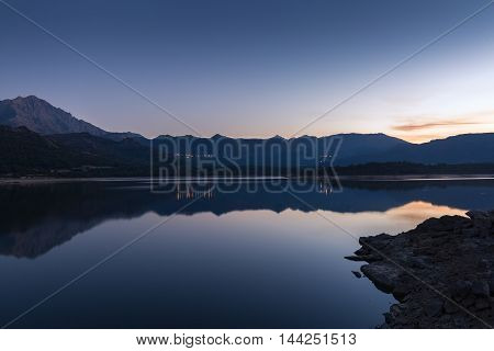 Dusk over the Lac de Codole near Reginu in the Balagne region of Corsica with mountains in the background and village lights in the distance and reflected in the mirror surface of the lake