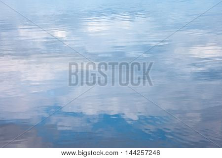 Water surface with reflected clouds. Natural background
