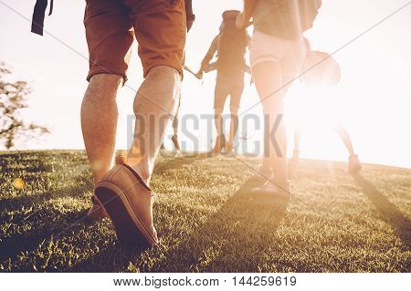 Keep moving! Close-up rear view of young people with backpacks moving by green grass with sunrise in the background