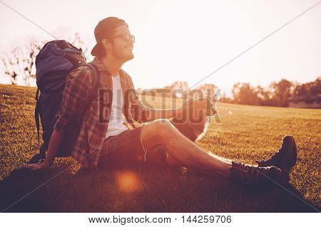 Traveler with his dog. Cheerful young man with backpack petting dog while kneeling on the green grass outdoors