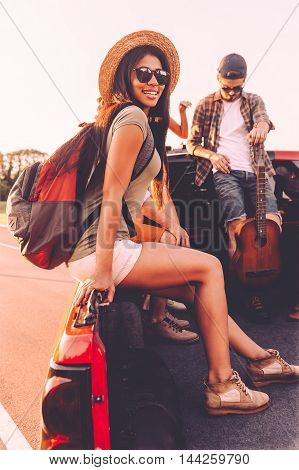 Ready for road trip. Beautiful young mixed-race woman with backpack looking at camera and smiling while sitting together with her friends in pick-up truck outdoors