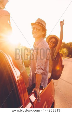 In search of adventures. Beautiful young cheerful people enjoying road trip in pick-up truck together