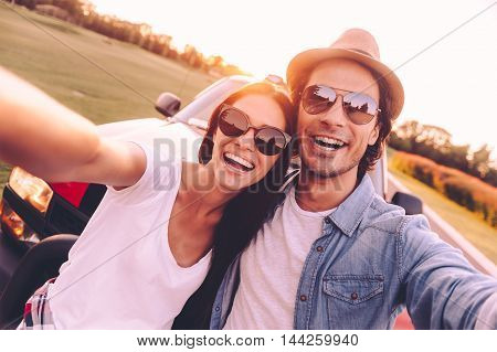 We love selfie! Beautiful young couple bonding to each other and leaning at their pick-up truck while making selfie