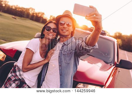 Selfie time! Beautiful young couple bonding to each other and leaning at their pick-up truck while making selfie