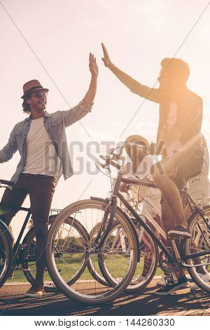 High five to friend. Low angle view of cheerful young people standing near their bicycles on the road while two men giving high five to each other