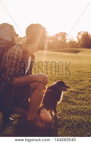 Traveler with his friend. Cheerful young man with backpack petting dog while kneeling on the green grass outdoors