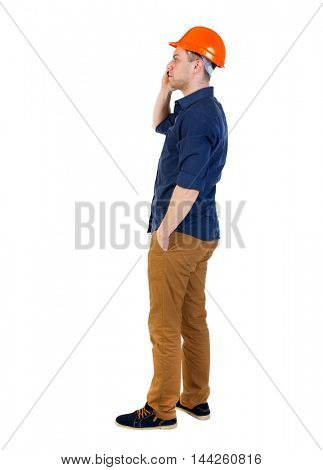 Backview of business man in construction helmet stands and enjoys tablet or using a mobile phone. Isolated over white background. a man in a blue shirt and a helmet on the phone.