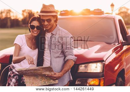 Examining map together. Beautiful young couple bonding to each other and leaning at their pick-up truck while examining map together