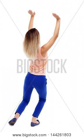 back view of woman protects hands from what is falling from above. Isolated over white background. Blonde in blue pants shove something up