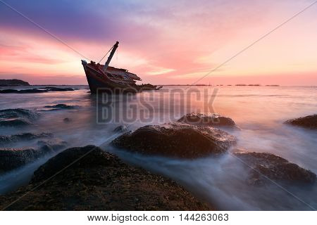 An old shipwreck or wrecked boat abandoned stand on beach