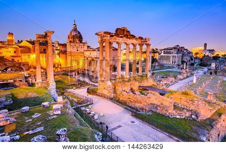 Rome Italy. Stunning twilight view of Roman Forum ancient ruins seen from Capitoline hill with Colosseum.