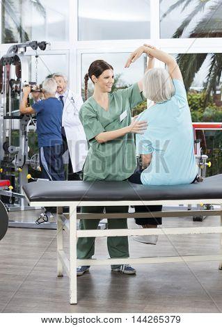Nurse Assisting Senior Woman In Arm Exercise In Rehab Center