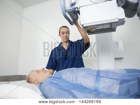 Radiologist Adjusting Xray Machine Over Man