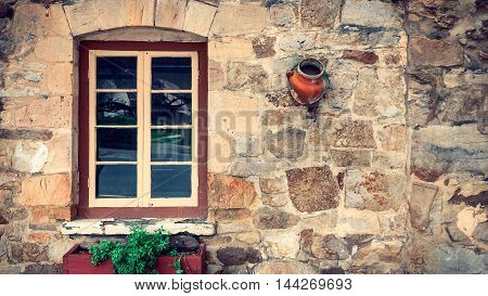 Grungy look of old house wall with window and flower pots in the town of Hahndorf Adelaide Hills area South Australia.